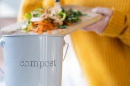 close-up-of-woman-making-compost-from-vegetable-leftovers-in-kitchen