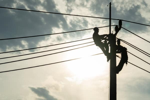 electrician worker climbing electric power pole