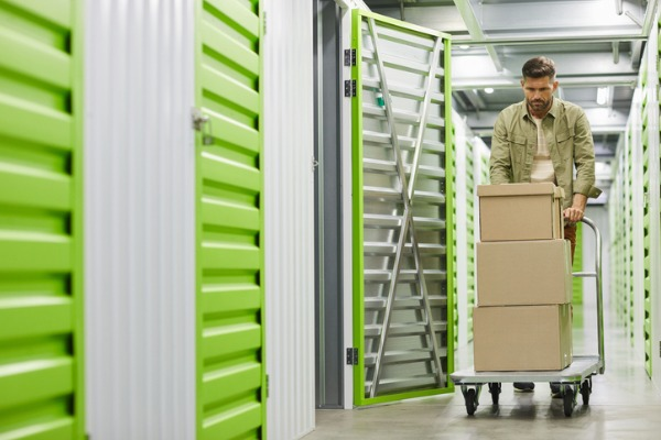 man moving boxes in self storage unit