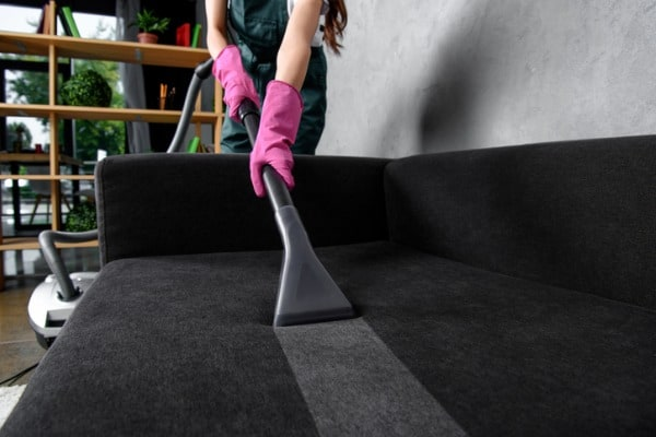 partial view of woman in rubber gloves cleaning furniture with vacuum